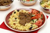 Beef madras curry served with saffron, raisin and roast cashew nut pilau rice and a salad of tomato,
