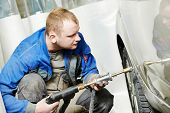 stock photo of peen  - auto repair man worker flatten and align metal body car with hammer in automotive industry - JPG