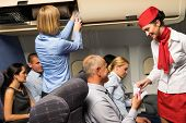 stock photo of cabin crew  - Air stewardess check passenger ticket in airplane cabin smiling - JPG
