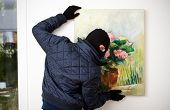 stock photo of felons  - Thief stealing the piece of art from gallery of art.
