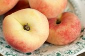image of peen  - Donut Peaches also known as Saturn peaches on a antique plate.