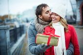 stock photo of sweetheart  - Image of affectionate guy kissing his girlfriend while giving her present outside - JPG