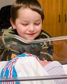 stock photo of baby delivery  - Excited boy meets his infant sibling for the first time after delivery at hospital - JPG