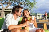 Постер, плакат: Woman drinking alcohol Mai Tai drink on Hawaii at beach club at sunset Beautiful girl enjoying alco