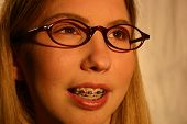 stock photo of pubescent  - A pretty teen with braces and black glasses smiling - JPG