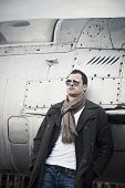 stock photo of fighter plane  - Male fashion model in front of a fighter plane - JPG