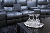 stock photo of home theater  - black executive leather home theater chairs with wine glasses on tray on black table - JPG