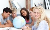 Teenagers In A Library Working With A Terrestrial Globe