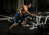 pic of execution  - very power athletic guy execute traction with dumbbells exercise on broadest muscle of back in sport hall - JPG