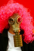 stock photo of rubber mask  - Funny Person In Gas Mask and artificial red Hair