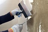 foto of putty  - Process putty gray concrete wall with two metal spatulas - JPG
