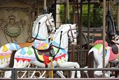 stock photo of merry-go-round  - White toy horses on a carousel - JPG