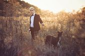 stock photo of greyhounds  - Young attractive man in suit and tie with a greyhound dog in autumn outdoors - JPG
