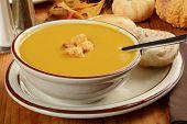 foto of butternut  - A bowl of butternut squash soup with dinner rolls - JPG