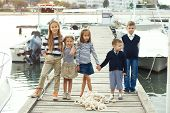 image of marines  - Many fashion kids wearing navy clothes in marine style walking in the sea port and holding hands - JPG