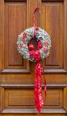 stock photo of alsatian  - Detail of a traditional Alsatian Christmas decoration on a wooden door - JPG