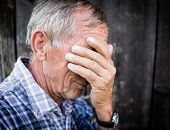 stock photo of grief  - Desperate senior man suffering and covering face with hands in deep depression - JPG