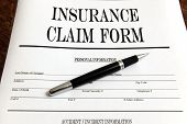image of reimbursement  - blank insurance claim form and pen on a desk