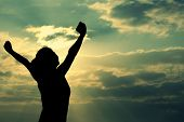 stock photo of open arms  - freedom woman open arms under the sunrise at seaside - JPG