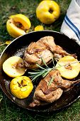 image of quail  - Roasted quails with quince on a cast iron skillet outdoor vertical - JPG
