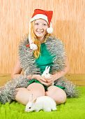 stock photo of tawdry  - teen girl in santa hat with two pet rabbits - JPG