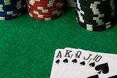 stock photo of flush  - spades straight flush with poker chips on green table - JPG