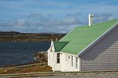 stock photo of falklands  - White building with green roof next to the sheltered bay at Stanley - JPG