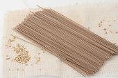 foto of bundle  - bundle of Japanese soba noodle with buckwheat groats scattered - JPG