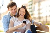 stock photo of sitting a bench  - Couple sharing media in a smart phone sitting in a bench in a park with buildings in the background - JPG