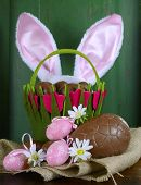image of easter eggs bunny  - Happy Easter basket with bunny ears of chocolate Easter eggs on burlap canvas against a green wood background - JPG