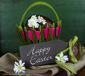stock photo of easter basket eggs  - Happy Easter basket of chocolate Easter eggs on burlap canvas against a green wood background - JPG