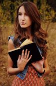 picture of auburn  - cute young woman with long auburn hair in the autumn forest reading a book - JPG