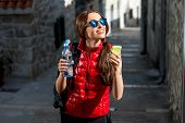 foto of knapsack  - Young woman in red sportswear looking where to go with smart phone traveling in the old city center - JPG