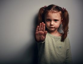 image of angry  - Angry kid girl showing hand signaling to stop useful to campaign against violence and pain on dark background - JPG