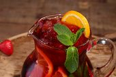 stock photo of jug  - Wine of Sangrija in a transparent jug on a wooden table with an orange and a strawberry - JPG
