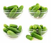 foto of foreshortening  - Glass bowl full of green fresh cucumbers isolated over white background - JPG