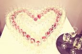 picture of champagne glasses  - Glasses of champagne in heart shaped setting - JPG