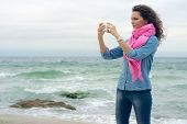 foto of denim wear  - Young woman with curly hair wearing a denim shirt makes the picture of the seaside - JPG