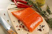 stock photo of salmon steak  - Salmon steak on wooden cutting board with herbs - JPG