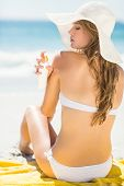 stock photo of sun-tanned  - Pretty blonde woman putting sun tan lotion on her shoulder at the beach - JPG