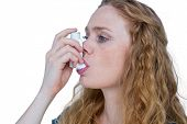 stock photo of asthma inhaler  - Pretty blonde using an asthma inhaler - JPG