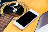 picture of risque  - Close up mobile and earphone on guitar - JPG