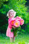 stock photo of little young child children girl toddler  - Little cute girl with peony flowers - JPG