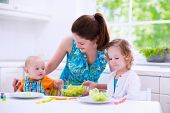 pic of cook eating  - Young mother and two children cooking in a kitchen - JPG