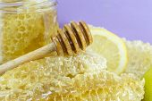 picture of decoupage  - Honeycomb dipper and lemon close up on a handmade decoupage table - JPG