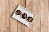 stock photo of cake-ball  - Fresh chocolate ball cakes sprinkled with colorful sugar balls - JPG