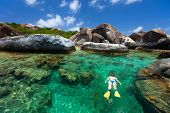 image of virgin  - Young woman snorkeling in turquoise tropical water among huge granite boulders at The Baths beach area major tourist attraction on Virgin Gorda - JPG