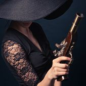 foto of pirate  - girl pirate with ancient pistol in hand on a black background - JPG