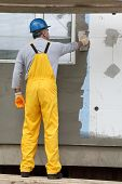 picture of trowel  - Worker spreading mortar over styrofoam insulation and mesh with trowel - JPG