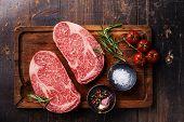 picture of ribeye steak  - Two Raw fresh marbled meat Black Angus Steak Ribeye and seasonings on dark wooden background - JPG